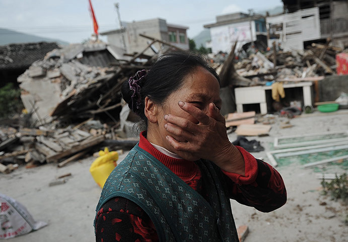 A woman reacts as her house is damaged in an earthquake