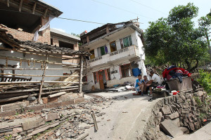 Residents rest outside damaged houses in Longmen township